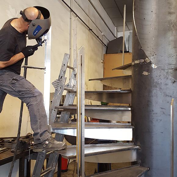 Trabajador soldando escalera de caracol en Artmeval